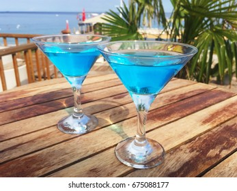 Two martinis on a summer terrace with palm trees and a beach