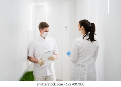 Two masked doctors a man and a woman walk down the corridor. A new modern hospital during the pandemic