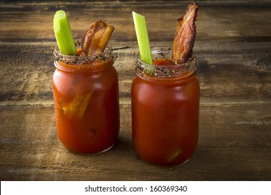 Two mason jar Bloody Marys or Caesars  with  bacon on wood background
