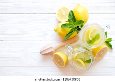Two mason jar glasses of homemade refreshing lemonade with slices of organic ripe lemon, whole and halved, juicer, muddler, squeezer on a rustic white wooden background. Close up, top view, copy space