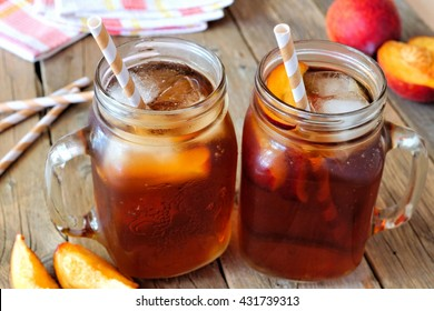 Two mason jar glasses of homemade peach iced tea on a rustic wood background