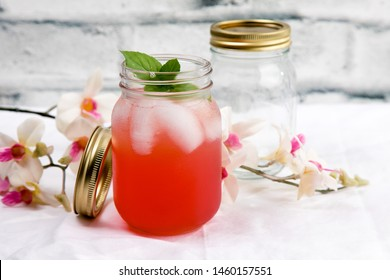 two mason jars on a table cloth with a pink vodka cocktail with a mint leaf and one empty and flowers by a white brick wall with lime wedges