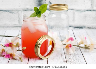 two mason jars on a wood table with a pink vodka cocktail with a mint leaf and one empty and flowers by a white brick wall with lime wedges
