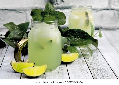 two mason jars on a wood table with a lime vodka cocktail with a mint leaf and one empty and flowers by a white brick wall with lime wedges