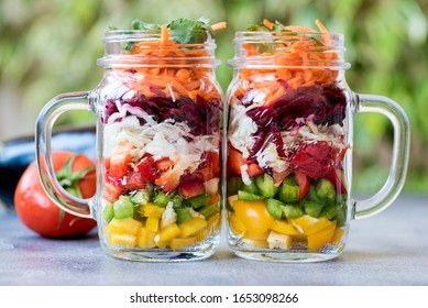 Two mason jars packed with colourful layered fresh vegetable salad to bring to work