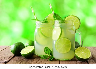Two mason jars of summer limeade on wood against a green outdoors background