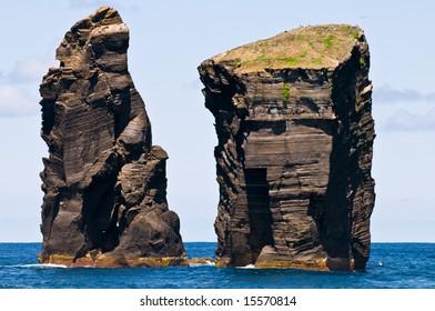 Two massive lava stone pillars raising from the Atlantic