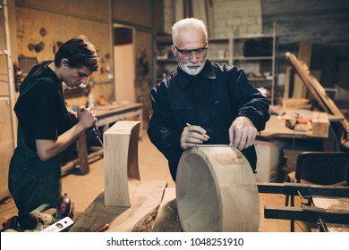 Two master carpenters working together in their woodwork or workshop.
