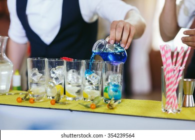 Two master mixologists creating drinks and cocktails at wedding reception