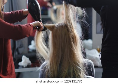 Two masters at the same time dried with hair dryers hair blonde model in beauty salon. Rear view.