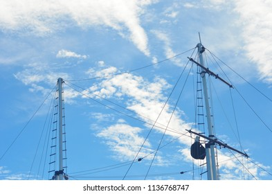 Two masts of a yacht are seen against a blue sky. They have no sails, and the rigging and rope ladders are easily seen. White clouds are in the sky.