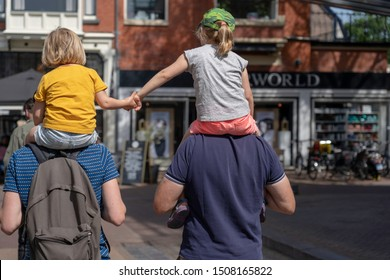 two mates walking side by side with there kids on there shoulders, kids holding hands