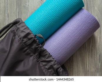 Two mats for yoga, fitness or Pilates. Mats in a gray backpack. Smooth surface for training