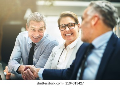 Two mature businessmen smiling and shaking hands together with a female coworker looking on while sitting at a table in an office