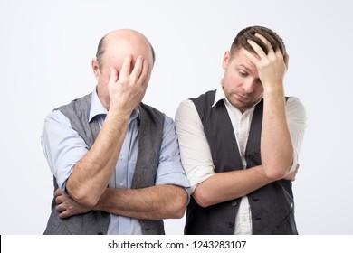 Two mature men with face palm gesture. Disappointed stressed out male making facepalm with hand.