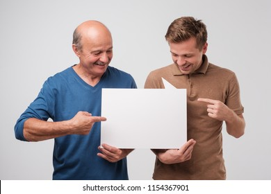 Two mature men father and son are holding a white empty billboard together. The friends are standing and smiling. Pay attention to profitable proposition