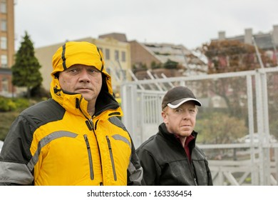 Two mature men out walking in an urban area on a dismal raining day in Victoria, British Columbia, with a wistful glance as they pass by the camera.