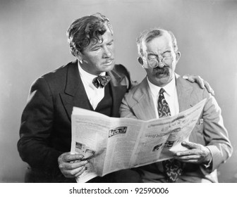 Two mature men reading a newspaper together
