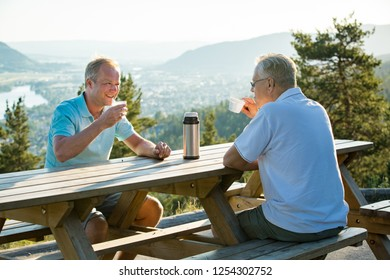 Two mature men sitting at wooden table on observation deck on top of mountain, drink hot coffee from thermos flask talking, smiling, laughing. Beautiful view of city in valley in haze. Norway, Drammen