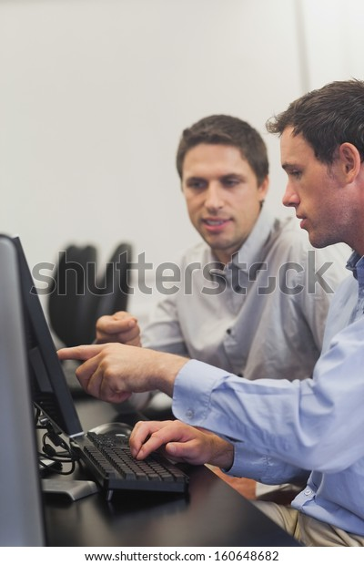 Two mature men talking while sitting in front of computer in computer class