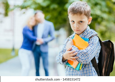 Two mature parents seeing their little child off to school. Sad pupil with satchel, in plaid shirt on foreground. Happy family and Loving of people theme. Protect support care good bye concept.