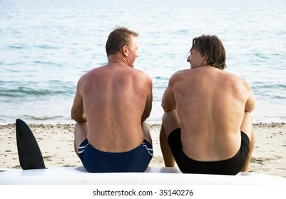 Two mature sporty men sitting on beach and chatting.