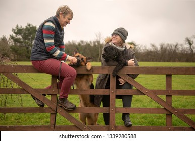 Two mature woman with dogs relaxing outdoors