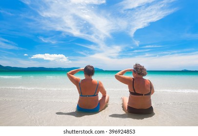 two mature woman in swimwear and enjoying  view islands relaxing on the beach.