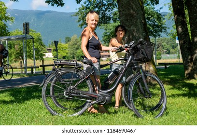 two mature women with bicycles in the countryside