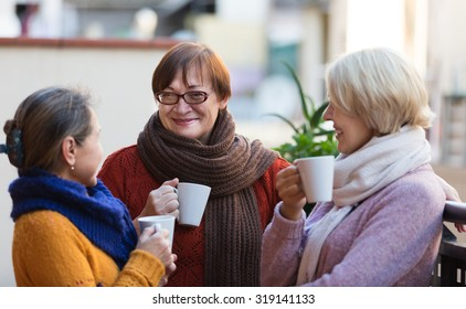 Two mature women drinking tea on balcony and smiling