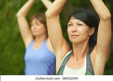 Zwei erwachsene Frauen, die im Sommer Yoga machen