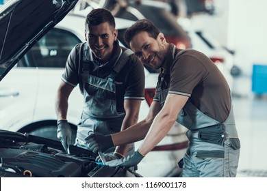 Two Mecanics Looking at Camera while Fixing Car. Portrait of Caucasian Handsome Happy Workers in Uniform and Gloves Repairing Automobile with Opened Hood. Repair Service Concept
