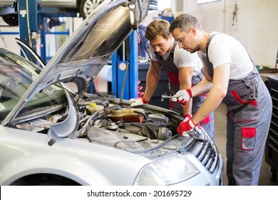 Two mechanics fixing car in a workshop