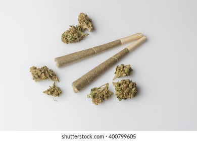 Two medical cannabis rolled joints with dried marijuana buds around on white background from above