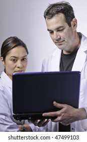 Two medical people looking at the laptop.