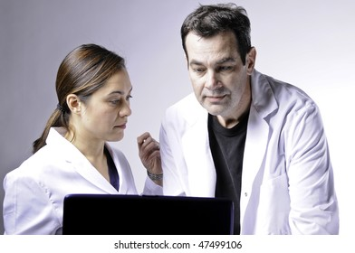 Two medical people looking at the laptop.Women is mixed race yuoung lady.