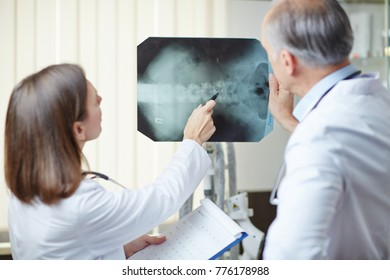 Two medical professionals having discussion of x-ray image of one of their patients