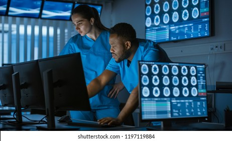 Two Medical Scientists / Neurologists, Talking and  Working on a Personal Computer in Modern Laboratory. Research Scientists Making New Discoveries in the fields of Neurophysiology, Science.