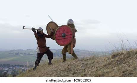 Two medieval warriors Viking are fighting with swords and shields in the meadow. Medieval Reenactment.