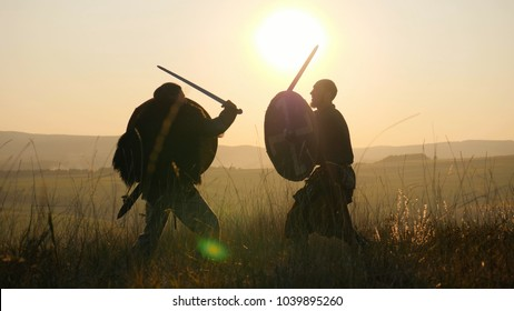Two medieval warriors Viking are fighting with swords and shields in the meadow. Medieval Reenactment. Contre-jour