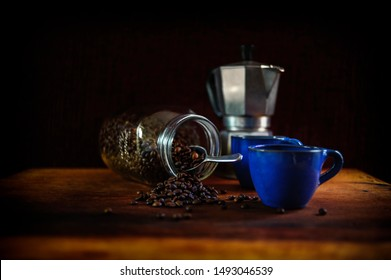 Two Mediterranean blue traditional coffee cups with coffee beans tumbling from a jar. Silver traditional cafetière in the background. Shot on a farmhouse style wooden table against a dark background.