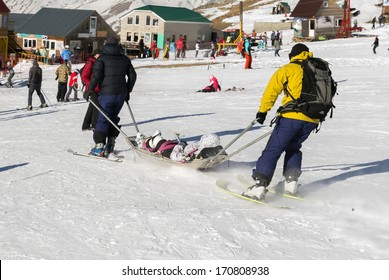 Two members of a ski patrol helping an injured skier down the mountain