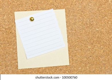 Two memo note papers pinned to a cork bulletin board with a brass tack.