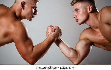 Two men arm wrestling. Rivalry, closeup of male arm wrestling. Two hands. Muscular men measuring forces, arms. Hand wrestling, compete. Hands or arms of man. Muscular hand. Clasped arm wrestling.