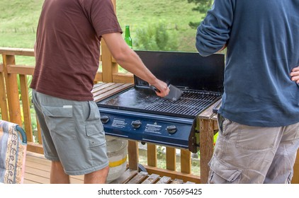 Two men at barbecue while  cleaning the grate