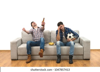 The two men with a beer and chips watch a football on the sofa
