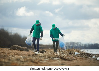 Two men with big sacks walking along river bank, picking up litter and putting it in those sacks