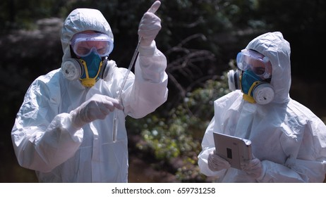 Two men in biohazard suits and masks sampling water from a stream or river pipetting a sample into a test tube for chemical analysis of pollutants.