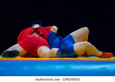 Two men in blue and red wrestling on a yellow wrestling carpet in the gym
