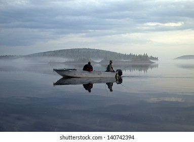 two men in a boat fishing on a calm lake